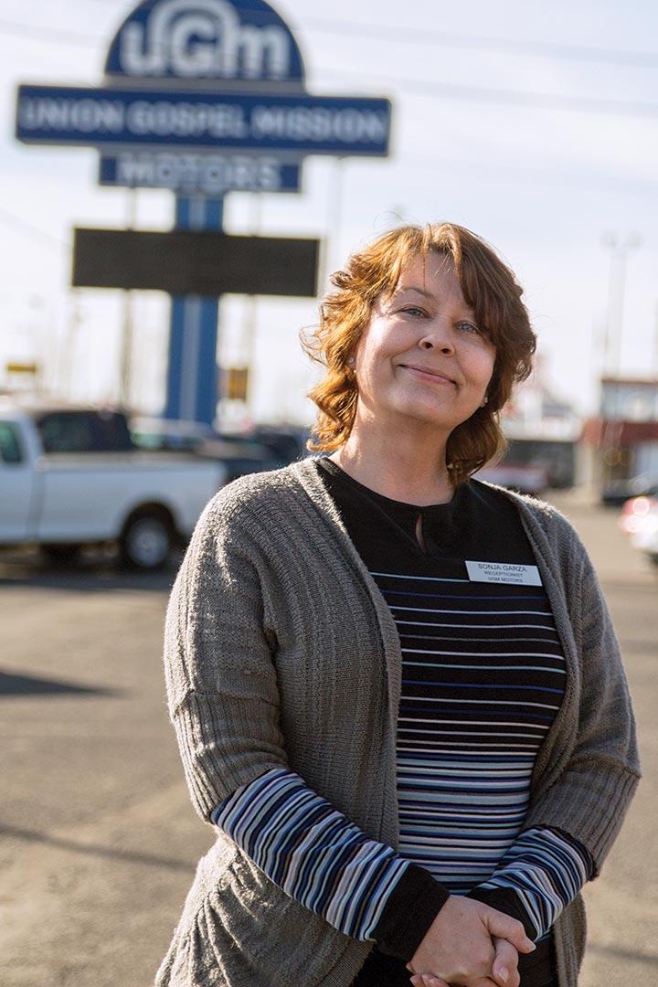 Sonja standing in UGM Motors car lot